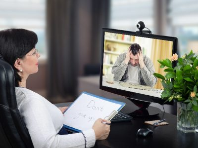 Depressed man is exceedingly despondent at first encounter with virtual psychotherapist.  The man sits with his head in his hands. Black-haired glasses psychotherapist watches and hears him on monitor. She holds written message– Dont give up. Horizontal shot indoors